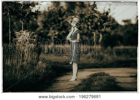 Classic Black And White Photo Of 1920S Summer Fashion Woman With Dress And Straw Hat Standing On Rur
