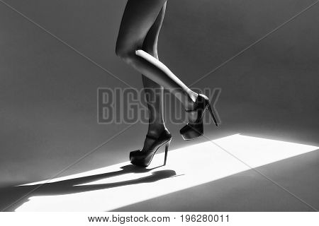feet or legs of woman in high heel shoes stand indoor on sunny floor black and white