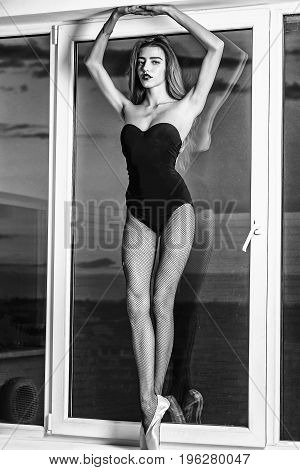 dancer young cute slim woman ballerina with long hair and legs in pointe shoes at window on sky background black and white