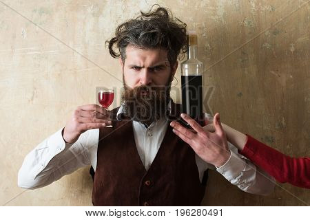 Hipster posing with wine glass and bottle on female hand. Unhappy man with long beard moustache on sad face and messy hair on beige wall. Alcohol abuse and alcoholism. Unhealthy lifestyle. Bad habits
