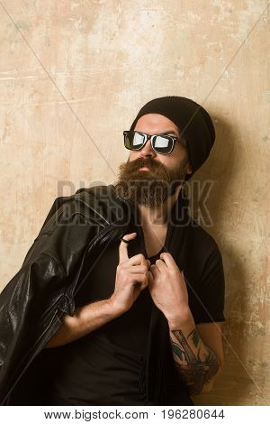 Guy with serious face. Hipster in leather jacket and hat with glasses. Fashion model on textured wall background. Biker fashion and beauty. Man with long beard and mustache.