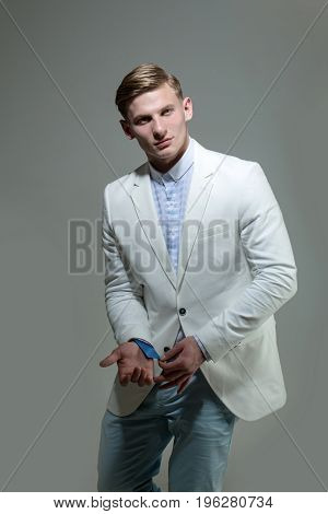 businessman or man in fashionable white jacket has blonde hair hold blue business card on grey background business ethic