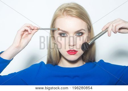 Woman With Brushes Applying Powder And Makeup On Face