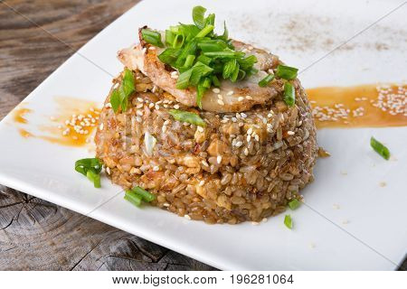 Fried asian rice with vegetable and meat served on a white plate