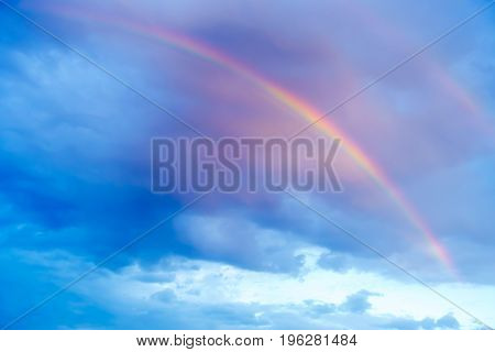 Cloudscape of rainbow and rainclouds during sunset.
