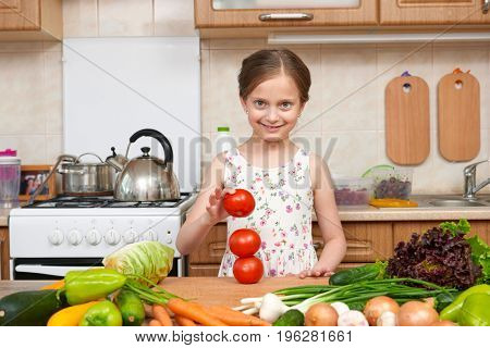 Child girl having fun with tomatoes. Home kitchen interior with fruits and vegetables. Healthy food concept