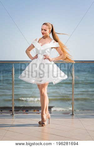 A cheerful female posing on a glass terrace on a blue sea background. The charming girl with long hair wearing a fantastic white dress. An attractive lady posing on high beige heels.