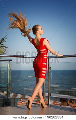 An extremely attractive young female posing on a sunny balcony on a bright blue background. A stunning lady in a saturated red dress with holes. A tall girl with a beautiful long dark blonde hair.