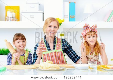 Loving family concept. Happy mother cooks with her daughters.