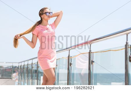 A wonderful young girl in a bright pink dress and with fashion glasses against the backdrop of an expensive and luxury hotel. A cute woman with long blonde hair is enjoying summer.