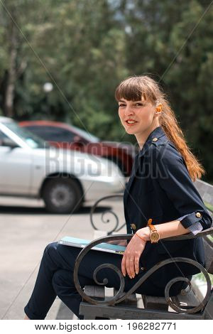 Business lady in a business suit sits on a bench