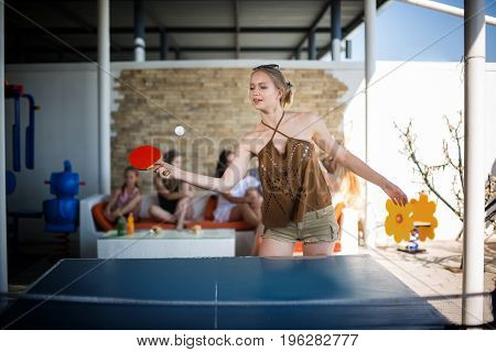 A nice and charming girl plays table tennis in her summer casual clothes at the entertaining center. A beautiful young woman is playing tennis. Sporty and cute girl plays table tennis.