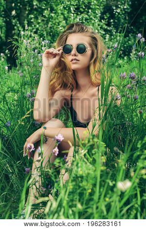 Pretty girl sits in the grass among the wild flowers. Summer day. Modern hippie, hipster style. Beauty, fashion outdoor.