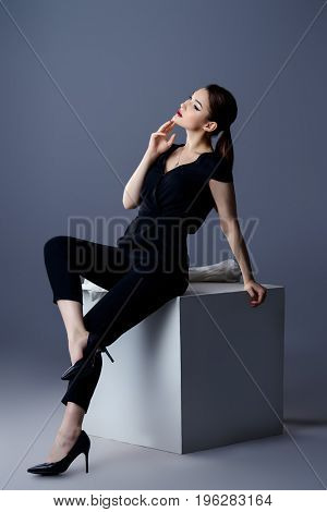 Fashion shot. Professional vogue model posing at studio. Collection of business clothes. Full length portrait.