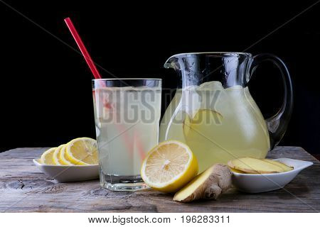 Lemonade drink glass and jar on a wooden table