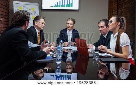 Group of businessmen sitting at table in office and having conversation.