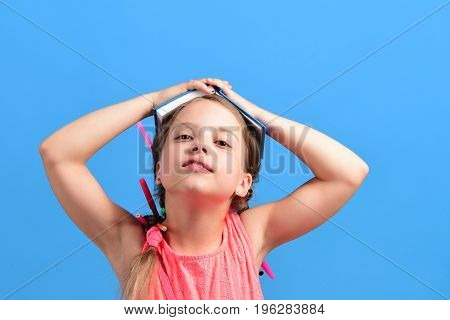 Girl Holds Open Book On Head With Hands Up