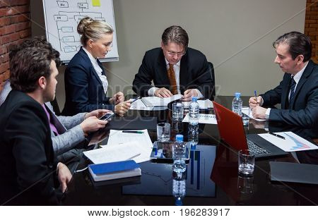 Group of people sitting at table in office during meeting.