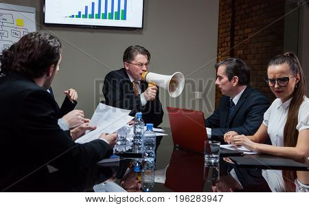 Man with loudspeaker shouting at employees at table during meeting.
