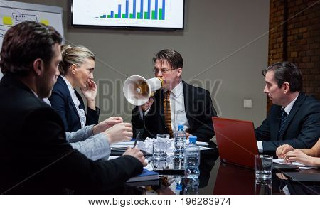 Angry boss shouting at loudspeaker while sitting at table with employees in office.