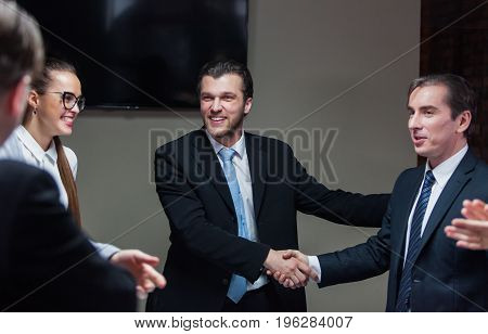 Smiling group of businessmen and two males shaking hands.