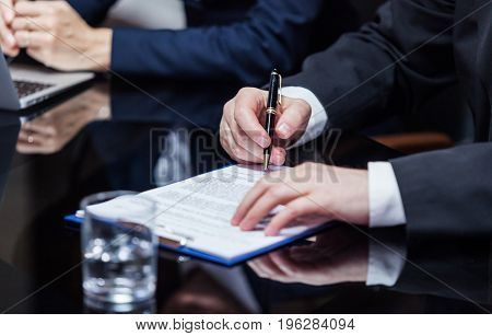Hands of a businessman sitting and signing the papers on the meeting.