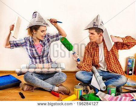 Repair family by happy couple building home. Mad woman and man in newspaper cap renovation apartment by painting tools. Newlyweds in the new apartment.