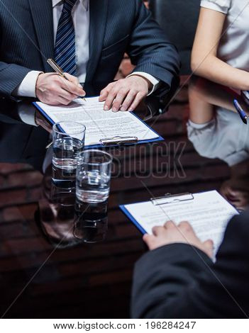 Hands of the businessmen sitting on the meeting and signing the contract.