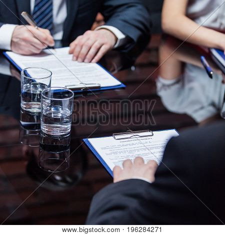 Two unrecognizable businessmen sitting on the meeting and signing the papers in the office.