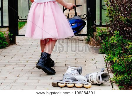 Active outdoor sport for kids. Young girl is holding a helmet for roller skating in a pink fluffy skirt, at the feet lie roller skates.Inline skates sport conceptual image.