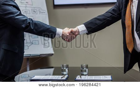 Crop shot of two businessmen in formal suit making deal and shaking hands on blurred background.