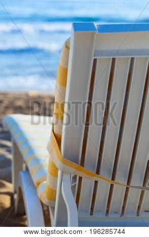 Sun bed on sandy beach of blue sea