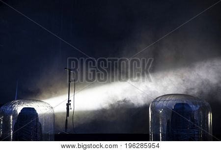 Microphone with spotlights with colored lights at a rock concert.