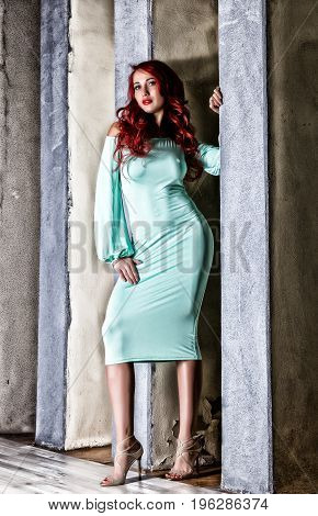 sexy beautiful redhead young woman with big boobs in a turquoise dress on a old gray wall background.