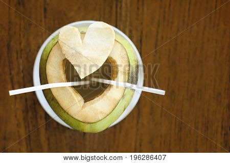Young healthy cutted coconut with a  straws on a wooden table. Fresh tasty exotic drink