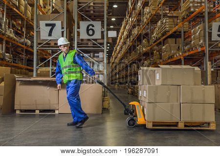 Warehouse worker dragging a cart with merchandise poster