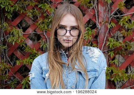 portrait of beautiful young woman in eyeglasses against wooden fence