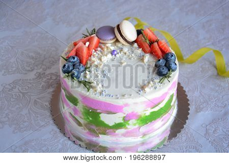 colorful homemade cake with berries and macaroon over white background