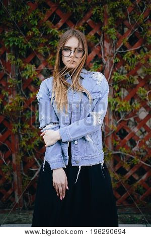 Fashion portrait pretty young woman. Long hair girl in denim jacket outdoor. Portrait of beautiful stylish young woman in blue jeans jacket posing against wooden fence