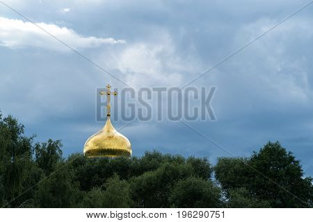 Golden dome of a church on a cloud background.