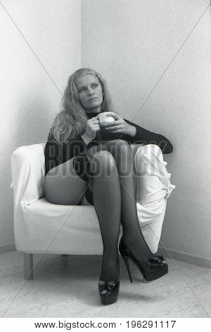 Vintage photo. A girl in stockings sits in a chair and holds a cup in her hands. Attention! The image contains a strong grain of the film!