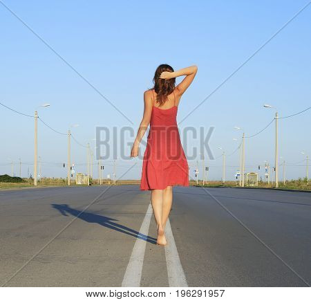 Beautiful female go away on empty road