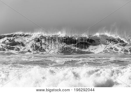 Waves upright sand water crashing ocean power closeup black and white contrasts.