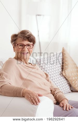 Smiling elderly lady sitting on a comfortable couch