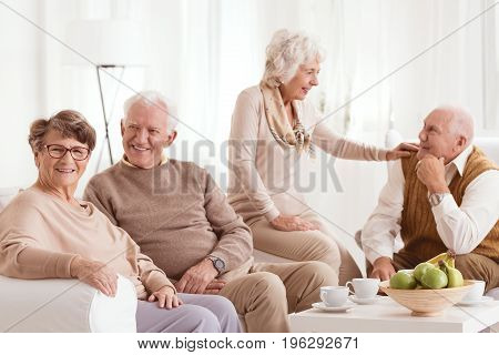 Family reminiscing about past by a cup of tea and bowl of fruits