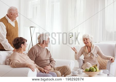 Old neighbors having a tea party while listening to a story