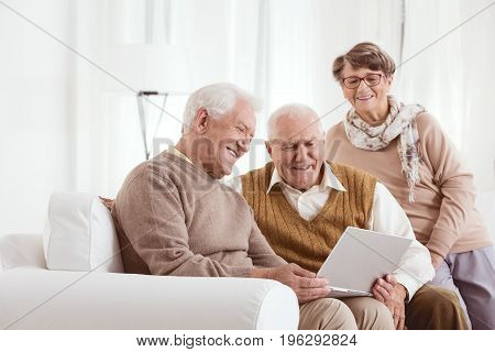Elderly man showing his new laptop to his family at retirement home