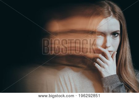 Girl with a distrustful look in her eyes holding a hand to her mouth