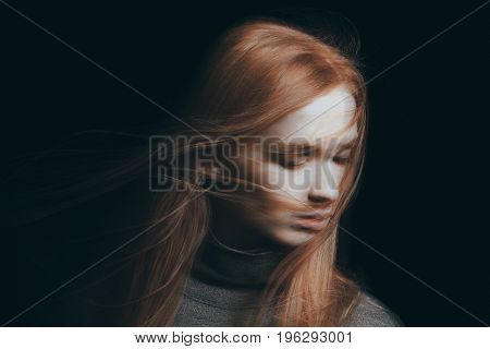 Young girl trying to find solace while her hair are falling on her face in a concept of depression