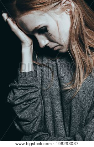 Depressed young girl in tears supporting her head on her hand